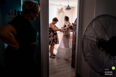 Nederlandse trouwfoto van de bruid die zich klaarmaakt tijdens een hete zomer in een kleine kamer