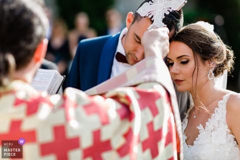Il sacerdote pone la croce sulle teste degli sposi nel luogo della cerimonia a Tsarsko
