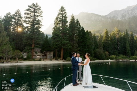 A bride and groom elope on the bow of a Lake Tahoe Boat Rides charter boat, officiated by the boat captain, under the peaks of Emerald Bay and gazing upon Vikingsholm Castle