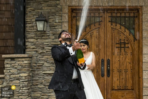 Wedding photography of a Washington	bride and groom celebrating with spraying some champagne