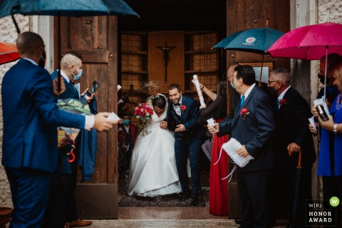 Rome wedding photography from Italy of the bride and groom exiting the church surrounded by umbrellas
