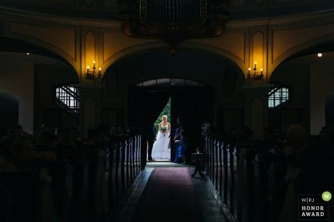 Fotografía de boda en Eslovaquia de Banska Bystrica mostrando a la novia antes de la ceremonia a punto de entrar