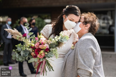 Domaine de Larchey, France wedding photo of a tender kiss with COVID masks on