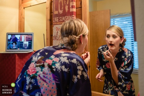 Northern California wedding image of a bride as she puts on lipstick in her robe as her friends watch on via a Zoom call on a laptop