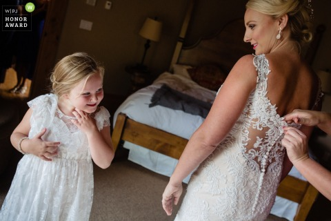 Lake Tahoe wedding image of a flower girl looking on as the maid of honor buttons up the back of the bride's wedding dress
