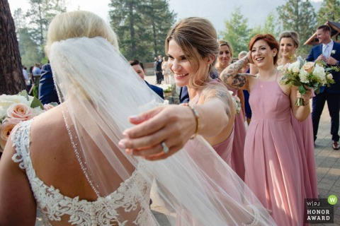 Squaw Valley wedding image of the maid of honor reaching out to hug the bride and congratulate her at the end of an outdoor wedding ceremony