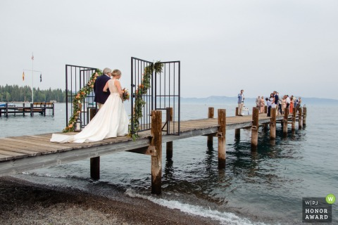 Lake Tahoe wedding image of the Father of the bride walking his daughter down the aisle for a wedding on a lakeshore pier