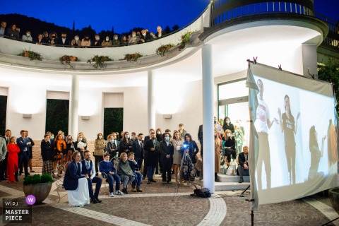The bride and groom watch a video together with their guests spread over two floors at the Villa Berardi, Vallio Terme