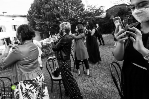 This Villa Angeli wedding image shows the bride's friends taking pictures before her official entry at her Pegognaga ceremony