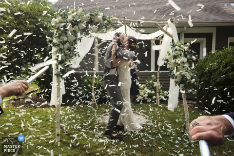 Bride and groom first kiss with confetti after their ceremony in eastern Massachusetts