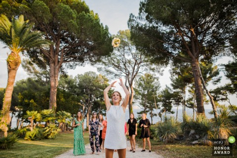 Outdoor wedding photography from the Ceremony location of La Ciotat of the ladies trying to catch the brides bouquet