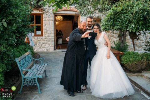 Bulgaria outdoor wedding photography from Tsarevo, Bulgaria of The priest taking selfie with the bride and groom