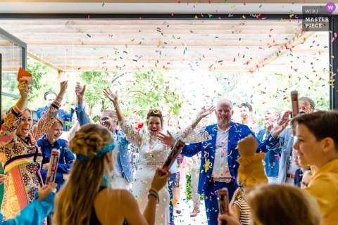 The bride and groom are hit with a confetti celebration at this Hengelo backyard wedding