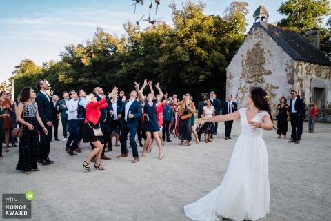 Photographie de mariage en plein air depuis le lieu de réception en Bretagne à Saint-Brieuc-le du lancer du bouquet