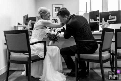 The groom kisses his brides arm as they wait to finalize payment in the city hall in San Diego