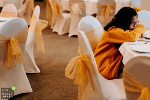 East Riding of Yorkshire wedding photography from the indoor England Ceremony location showing a Bored girl dressed in yellow complimenting the wedding decor