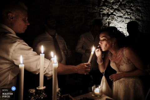 A cigar is lit for the bride at her Castello di Pomerio wedding in Italy