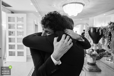 Italy black and white wedding photo from Da Vittorio restaurant, Brusaporto of The Groom hugging his father