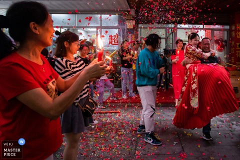 The bride's uncle carries the bride to the car, and the bride's relatives and friends light candles to see her off at this Chinese wedding day image