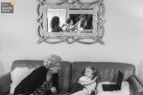 The bride is seen in the mirror on the wall getting ready for her wedding, while a child and older woman sit on a sofa with a laptop