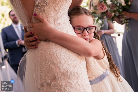 A young girl hugs the bride on her wedding day at The Estate at Eagle Lake NJ