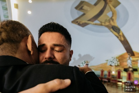 The thrilled groom embraces his father at the Catedral de Sao Carlos Borromeu on his wedding day