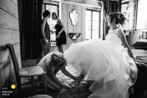 Getting the bride ready, her friends see the groom arriving outside in France