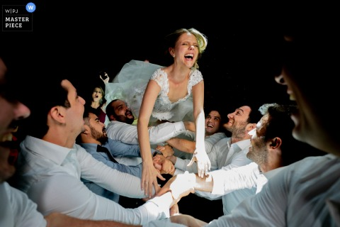 Bride jumps into the arms of men to catch her during her reception at the Allegro Buffet