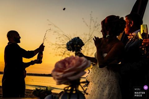 L'uomo migliore sta aprendo Champagne al tramonto sulla spiaggia di Papur sul Mar Nero