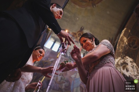 Church Rojdestvo Bogorodichno wedding ceremony photo of the maid of honor performing a ritual of changing wedding rings