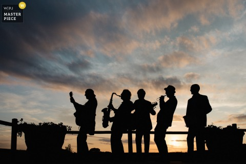 Silhouette wedding image of the band playing during sunset at the Tenuta Mocajo in Tuscany, Italy