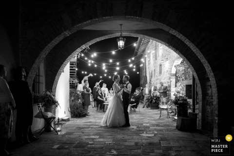 The bride and groom framed in an archway at the Castello di Buttrio while they have their first dance