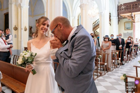 Church of Poussan France wedding image of the bride's dad kissing her hand after leading her down the aisle