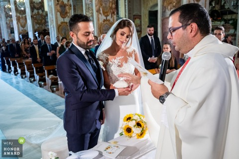 Basilica di Santa Caterina Alessandrina celebrant blesses the wedding rings, under the dreamy gaze of the bride in this Pedara ceremony photo