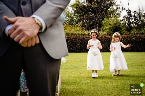 Cork, Ireland Outdoor wedding ceremony image of the flower girls walking the aisle while dropping petals
