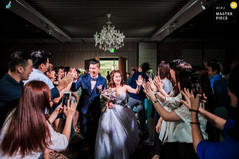 The newlyweds walked into the wedding venue and gave high fives to congratulate each other one by one at the wedding banquet in Taiwan