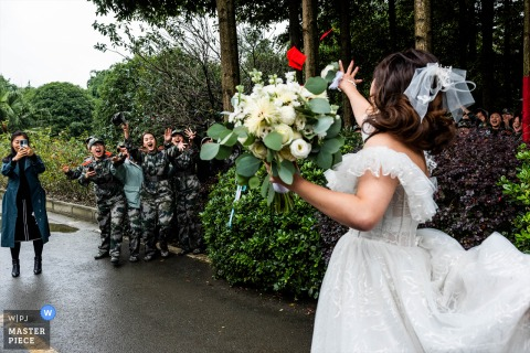 China bride is going to the ceremony site. On the way, she meets a group of military training students. They are wearing military uniforms. They are cheering for the bride. The bride throws a red envelope with RMB to them to express her gratitude.