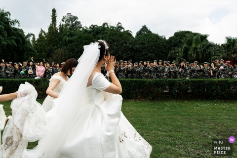 China newlyweds have finished the wedding ceremony. They are ready to leave the ceremony. There are many military training students around the ceremony. They also celebrate the wedding for the bride. This is unexpected. They greet the bride happily.