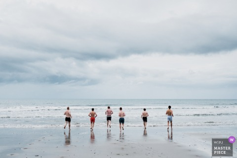 the groom and his groomsmen run into the sea for a morning swim before the day gets underway in Ballygalley, County Antrim, Northern Ireland