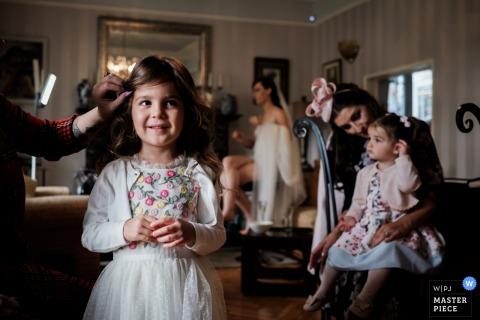 One of the couple's flower girls smiles has she has her hair done, as her little sister sits on her mother's knee, with the bride in the background in Larne, Northern Ireland