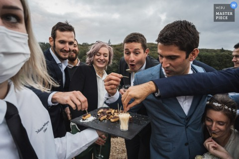 Wedding photo from a Miniac Morvan, France Cocktail hour of guests eating food from a vendor tray