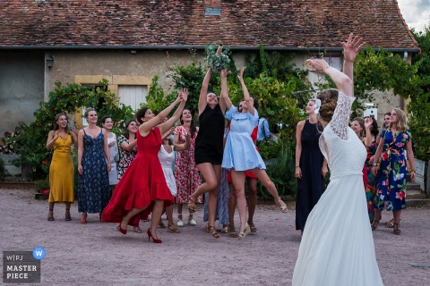 French brides throws her bouquet to the very eager single ladies who stretch out to catch it.