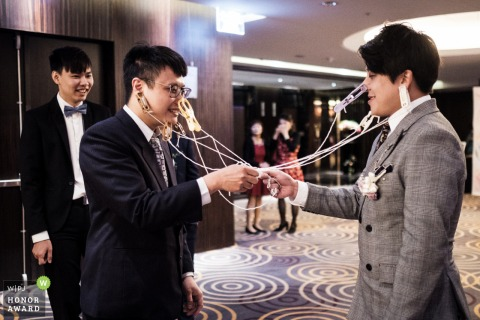 Splendor Hotel, Taichung, Taiwan wedding image of the groom and his groomsman putting clothespins on each other's face, as they are punished by the bridesmaids during the wedding games