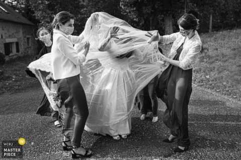 Wedding photography from France Serans of the bride getting help with her dress while heading to the Ceremony