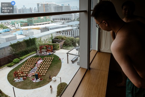 Wedding photography from Quanzhou Fujian of the groom taking a peek at the ceremony location from his hotel room