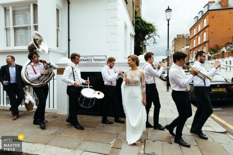 The bride stands waiting for her groom as a brass band plays behind her on the street outside of the Chelsea Town Hall