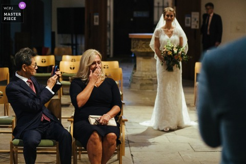 mother of the bride crying as the bride walks in to the ceremony at Streatham Church