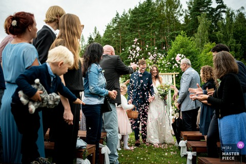 Samota Křemen wedding photo showing the rain of rose petals pouring down on the bride and groom after their outdoor ceremony