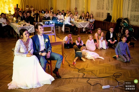 Valašská Polanka wedding photography of the bride and groom seated at the reception during the fun showtime
