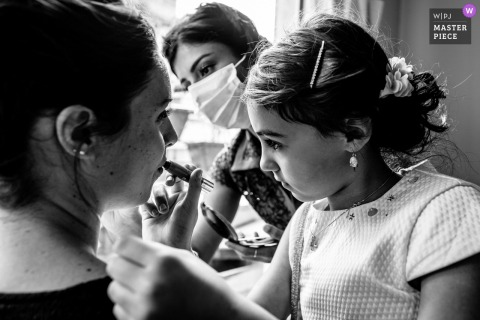 The Bride's daughter puts lipstick for her mother at their home in Courbevoie, France